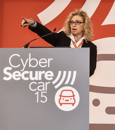 Image of a speaker with Cyber Secure Car branded lectern and backdrop